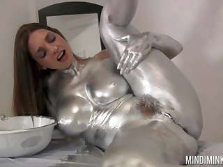 Nude beauty covers herself in silver paint for a odd solo